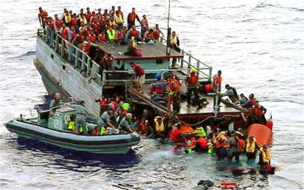 Australian navy personnel rescue asylum-seekers from a sinking boat off Christmas Island in October 2001
